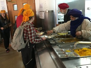 Receiving Langar, the free vegetarian meal Sikh Gurdwaras must provide daily, depending on their size